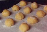 raw amaretti on a baking tray