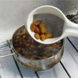 taking the almonds out of the boiling water with a sieve