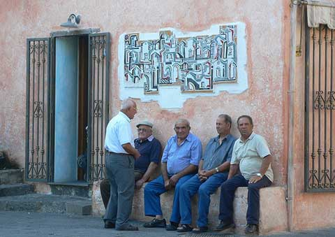 a group of sardnian men sitting in the piazza