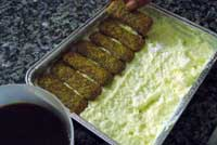 adding another layer of soaked sponge fingers to the tiramisu